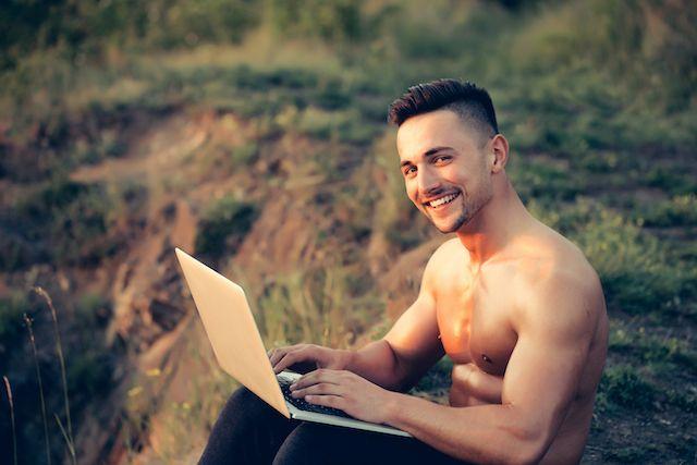 Mann sitzt am Laptop und chattet im Gay-Chat